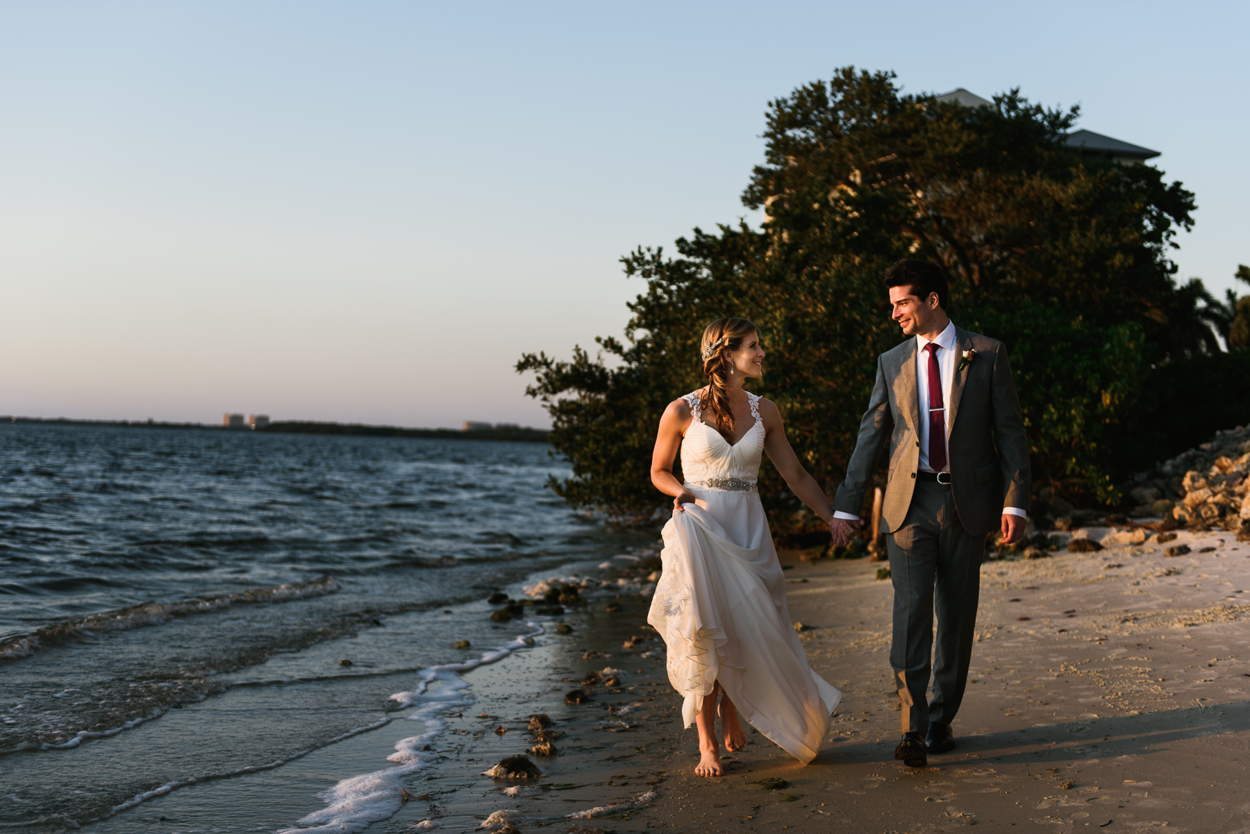 sanibel bride and groom walk beach at sunset