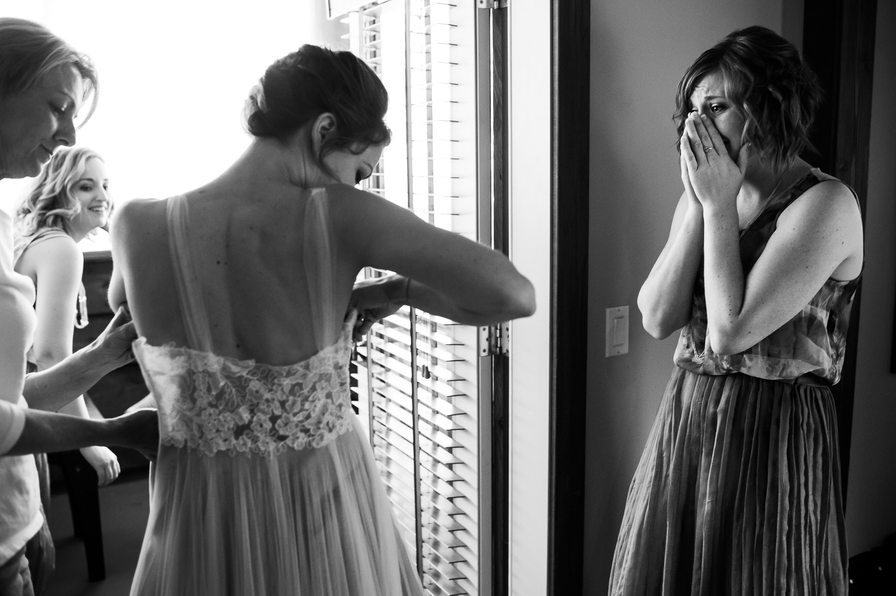 bridesmaid crying as bride gets in dress