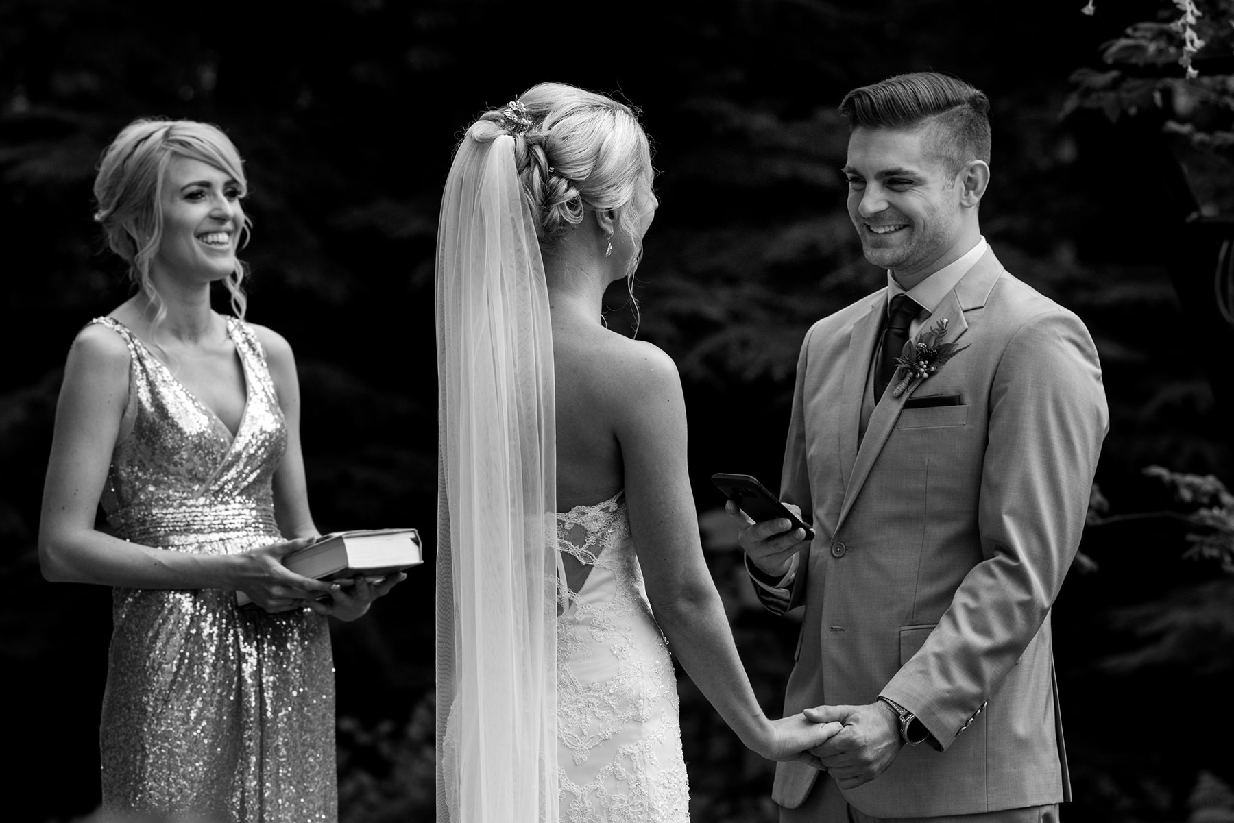 groom smiling while reading his vows