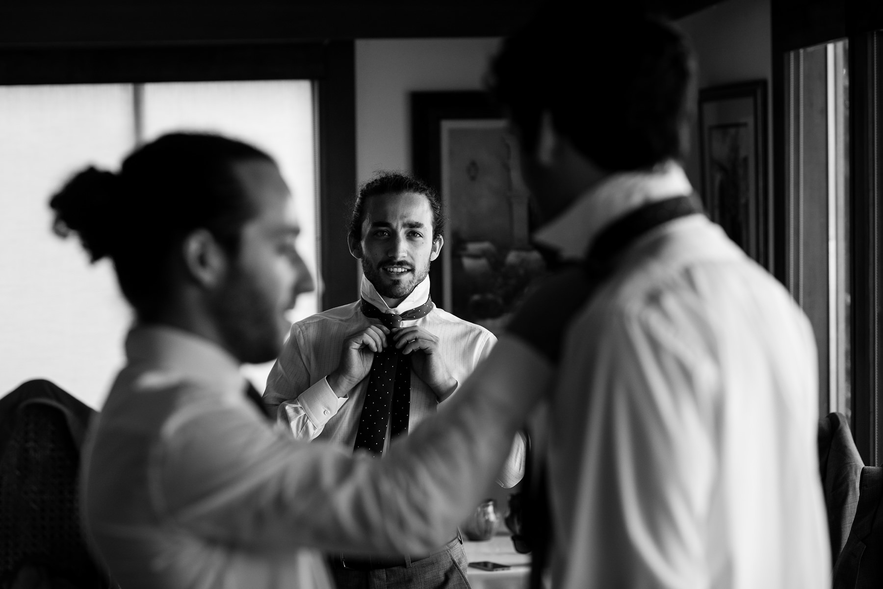 groomsmen putting ties on each other