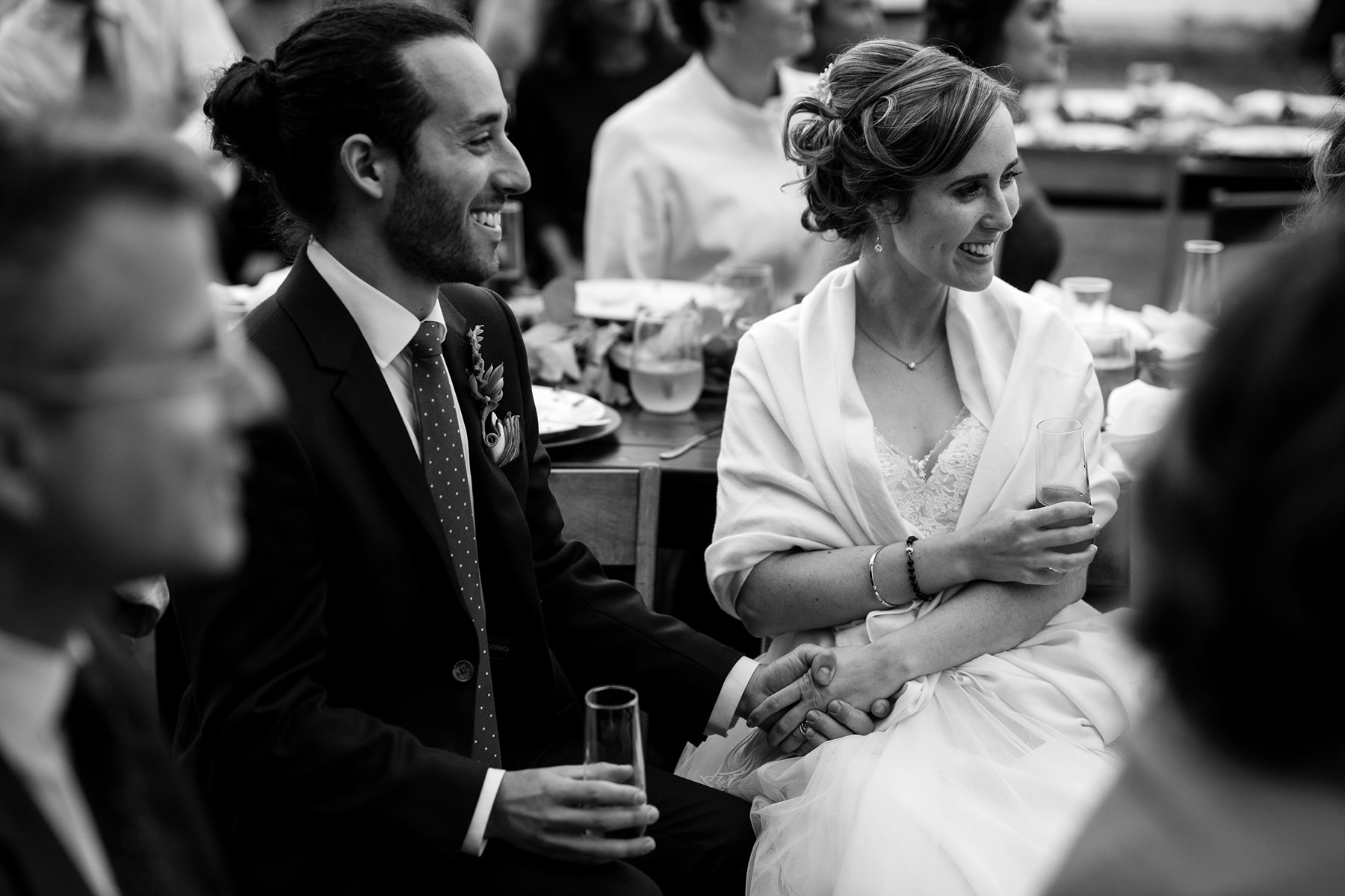 bride and groom hold hands while listening to wedding toasts