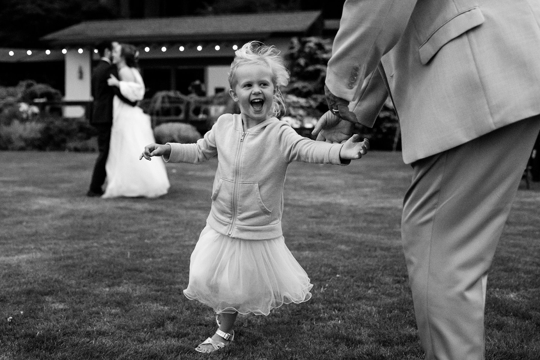 flower girl dancing with great grand father during wedding ceremony
