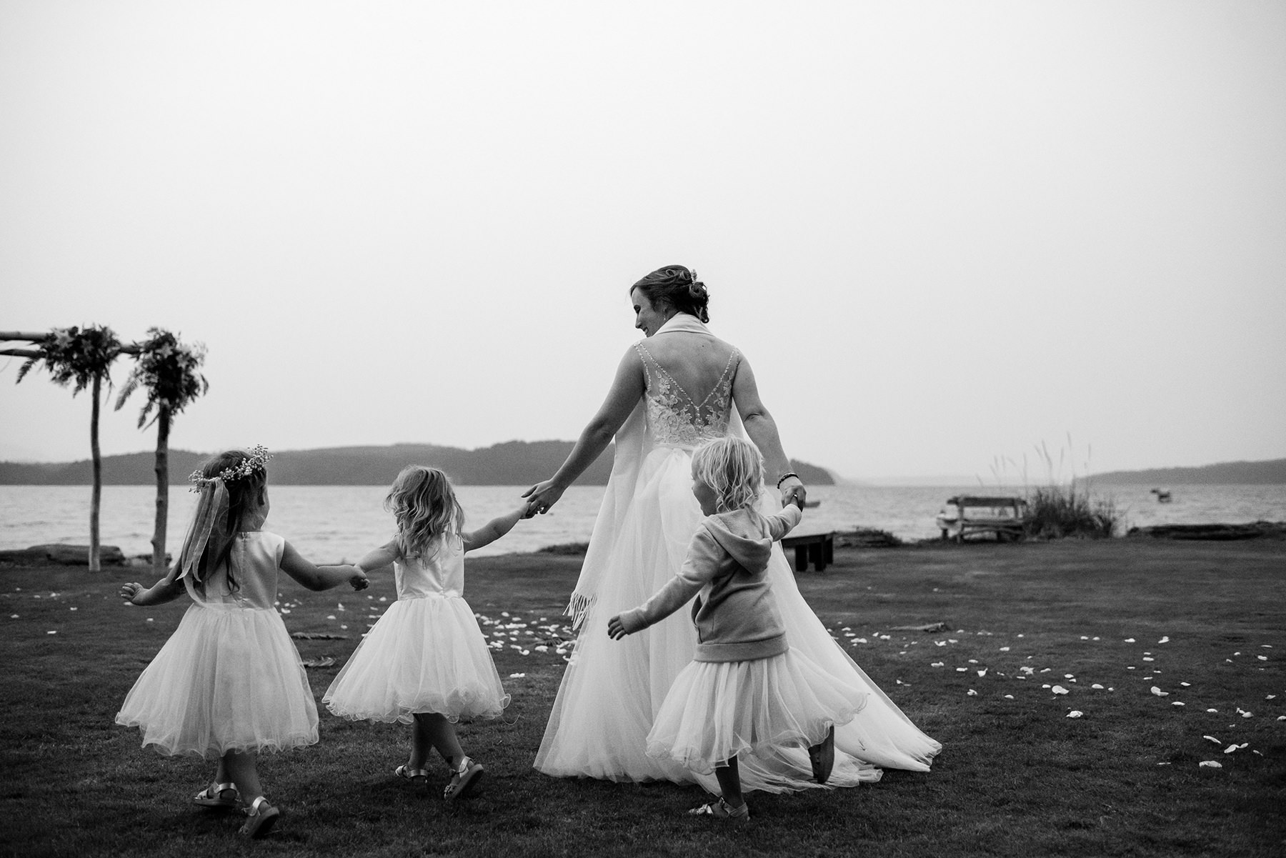 bride dancing with three flower girls