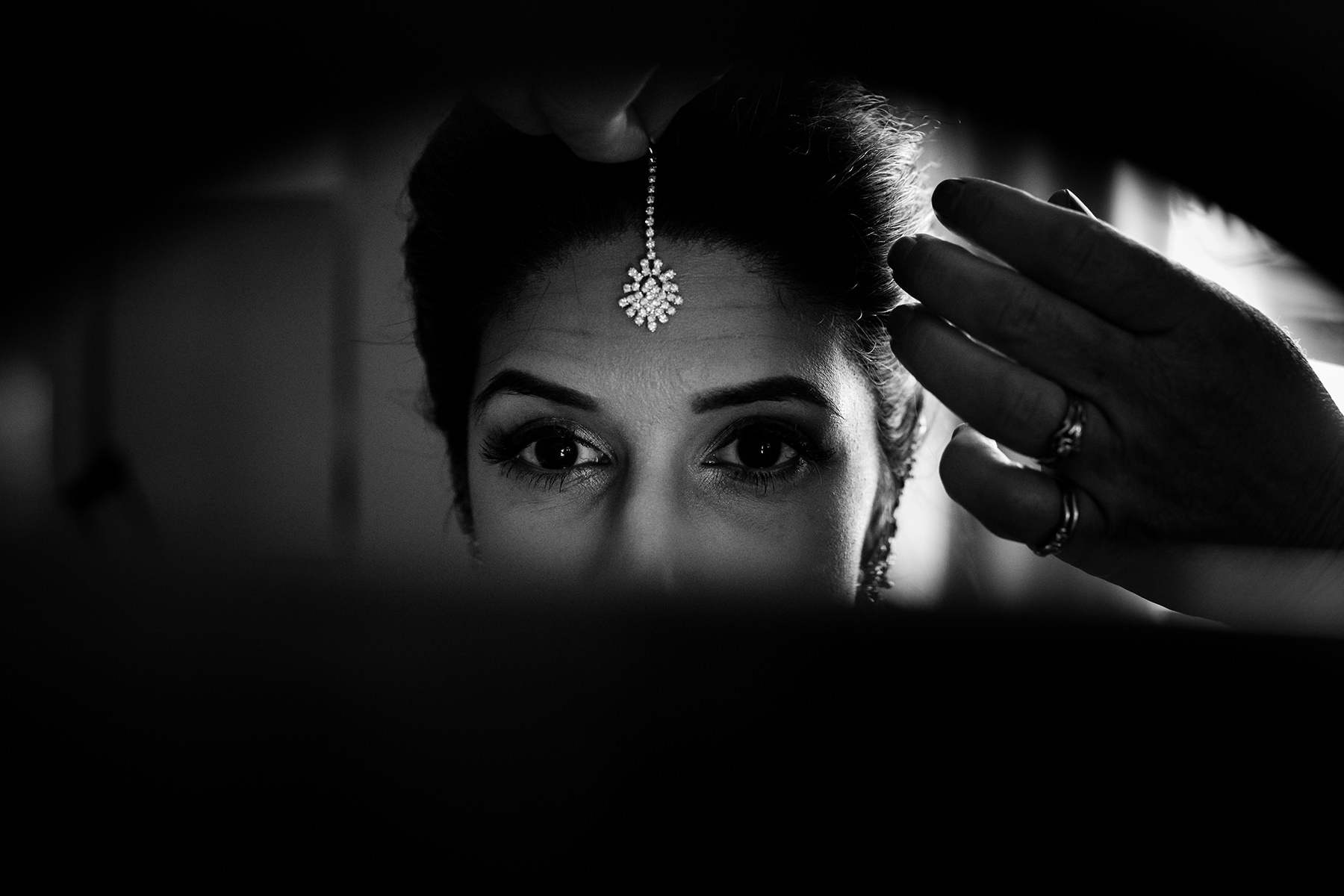 bride putting on tikka forward jewelry