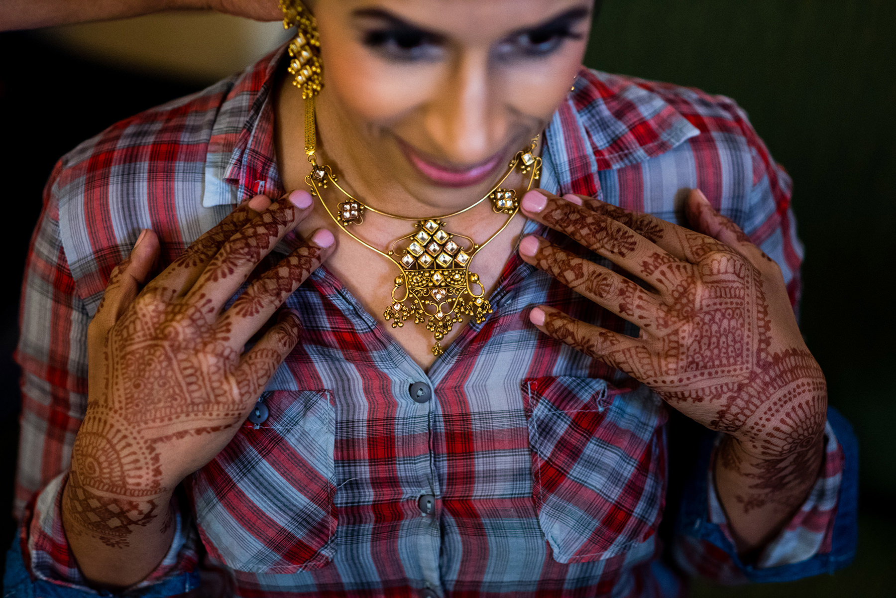 indian wedding bride putting on jewelry