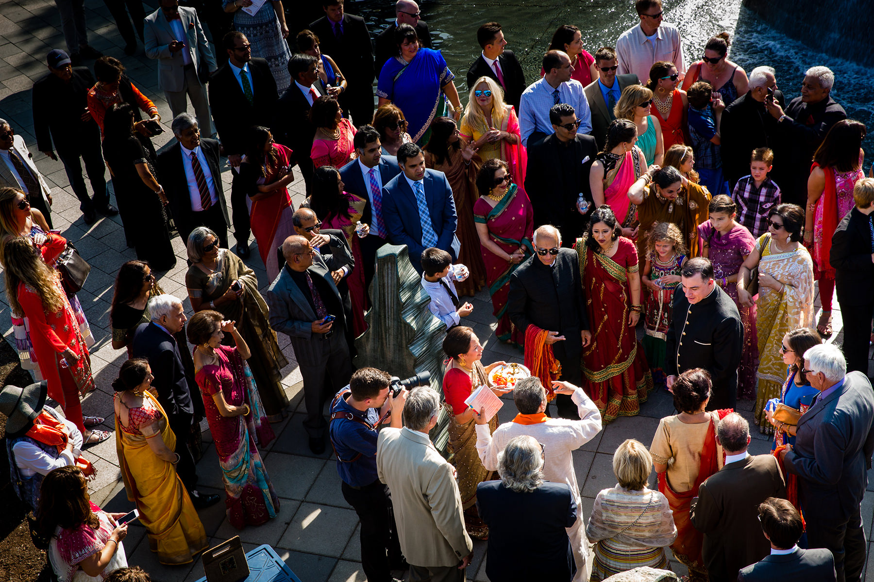 family gather around groom during start of hindu wedding ceremony