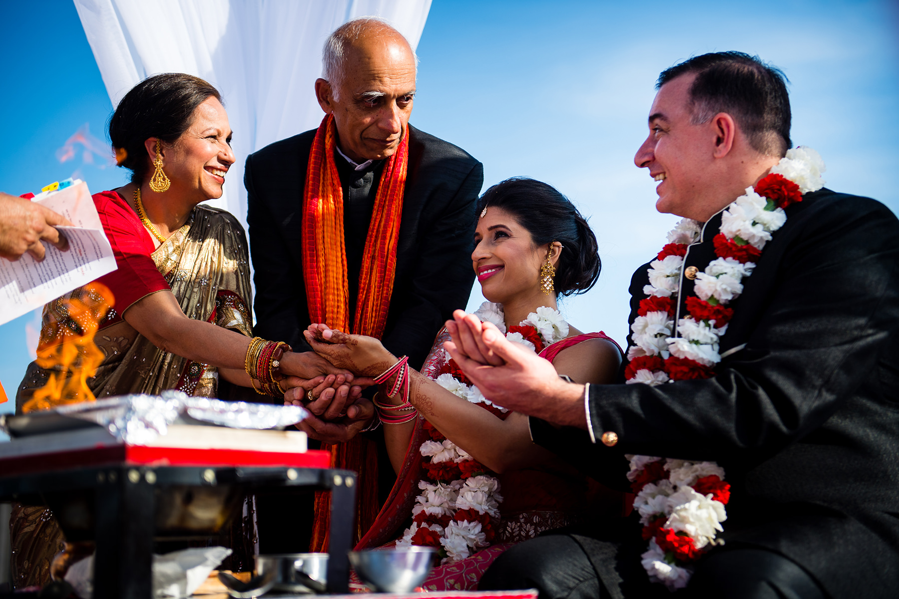 families holding hand together during hindu wedding